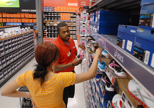Sports Authority employee Ernest Taylor shows Brittney Dominguez shoes at the store's opening at the Westfield Solano mall Thursday. (Robinson Kuntz/Daily Republic)