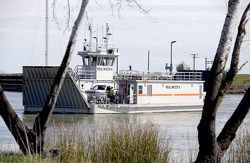 The Real McCoy II ferry makes its way across Cache Creek, taking a truck from Ryer Island Monday morning. The ferry is back in operation after being out of service since September of last year. (Brad Zweerink/Daily Republic)