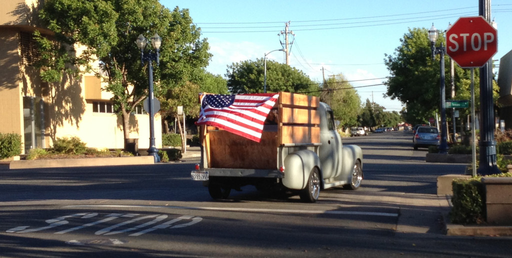 A truck with an American flag displayed at the back turns from Great Jones Street onto Texas Street in downtown Fairfield. (Glen Faison/Daily Republic)
