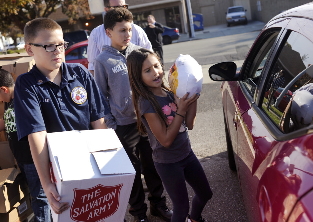 Salvation Army volunteers, from left to right, Raymond Lane, Darian Leon-Guerrero and Rylee Leon-Guerrero help hand out boxes of food and frozen turkeys for Thanksgiving, at the organization's Fairfield office, on Monday. (Robinson Kuntz/Daily Republic)