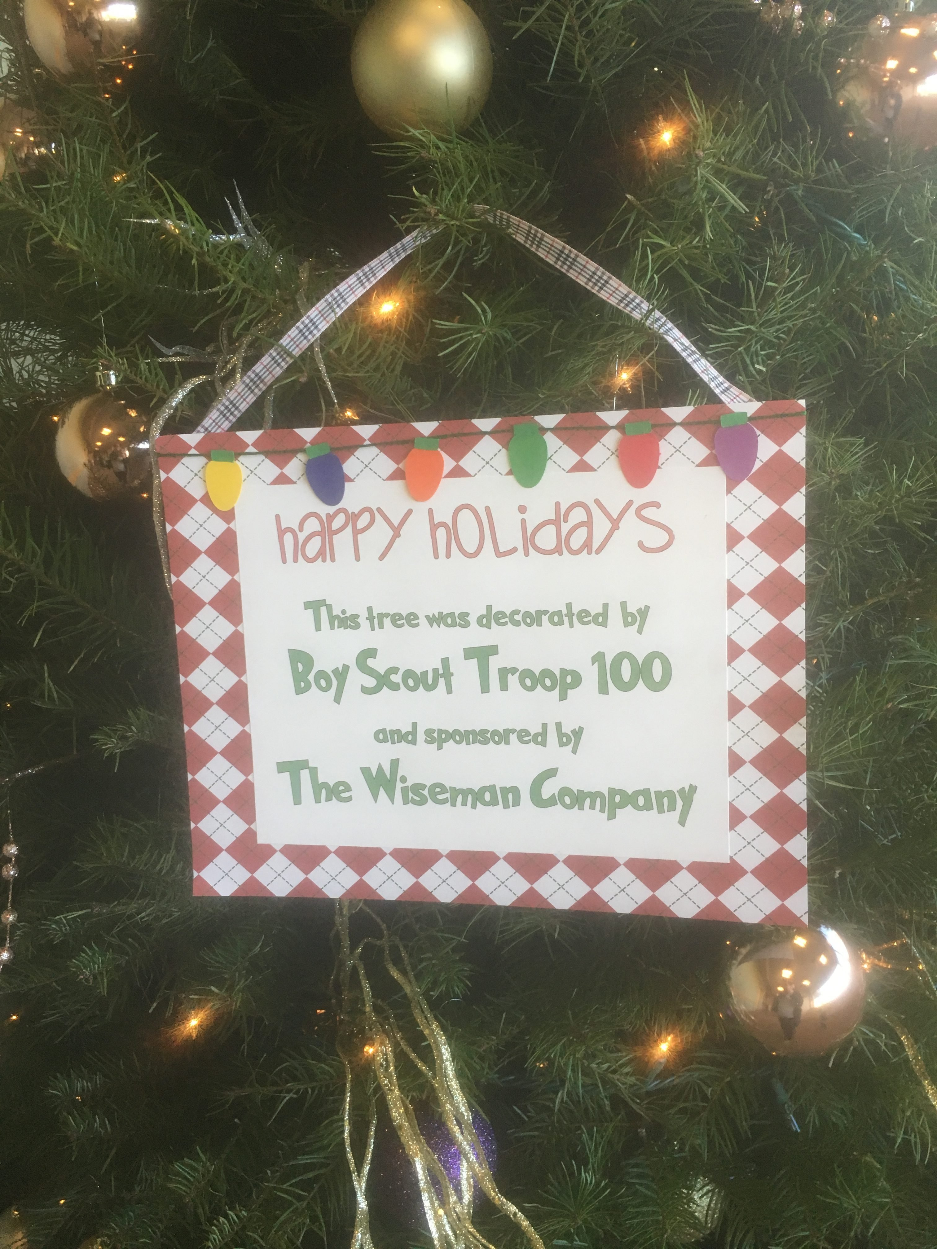 a sign shows the participation of boy scouts troop 100 in decorating a christmas tree courtesy photo - Boy Scout Christmas Trees